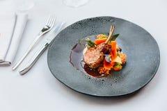 Moderne Franse keuken: De geroosterde het Lamshals & rek dienden met wortel, gele kerrie en lamssaus gediend in zwarte steenplaat royalty-vrije stock afbeeldingen