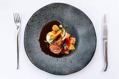 Moderne Franse keuken: De geroosterde het Lamshals & rek dienden met wortel, gele kerrie en lamssaus gediend in zwarte steenplaat royalty-vrije stock afbeelding