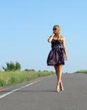 Moderne Frau, die auf eine Landstraße geht Stockfoto