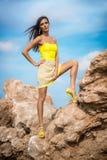 Moderne Frau, die auf einem Strand mit Felsen im Kleid aufwirft Lizenzfreie Stockfotografie