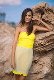 Moderne Frau, die auf einem Strand mit Felsen im Kleid aufwirft Lizenzfreie Stockbilder