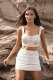 Moderne Frau, die auf einem Strand mit Felsen im Kleid aufwirft Stockfotos