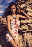 Moderne Frau, die auf einem Strand mit Felsen im Kleid aufwirft Stockfotografie