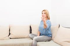 Moderne Frau, die auf einer Couch oder einem Sofa sitzt Stockfotografie