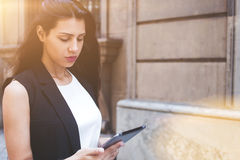 Moderne Frau, die digitalen Tablet-Computer für Navigation während des Schlenderns in der städtischen Landschaft verwendet Stockfotografie