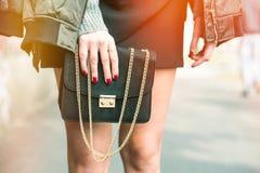 Moderne Frau, die eine olivgrüne Bomberjacke, eine goldene Uhr und eine schwarze modische Handtasche trägt Lizenzfreies Stockfoto