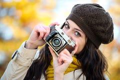 Moderne Frau, die Foto im Herbst mit Retro- Kamera macht Lizenzfreies Stockbild