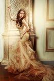 Moderne Frau in einem langen Goldkleid im schönen Innenraum Lizenzfreie Stockfotografie