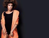 Moderne Frau im orange Mantel stockfotos