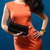 Moderne Frau im roten Abendkleid mit einer schwarzen Handtasche Stockfoto