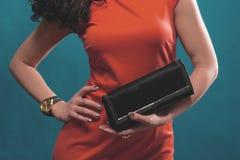 Moderne Frau im roten Abendkleid mit einer schwarzen Handtasche Stockbilder