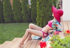Moderne Frau im roten Hut, der in einem roten Bikini aufwirft Stockfotos