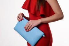Moderne Frau mit einer blauen Tasche und roten einem Abendkleid Lizenzfreie Stockbilder