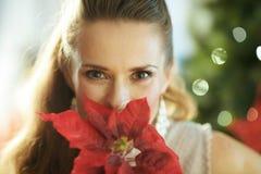 Moderne Frau mit roter Poinsettia nahe Weihnachtsbaum lizenzfreie stockfotografie