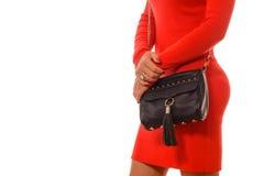 Moderne Frau mit schwarzer Tasche in den Händen und im roten Kleid Stockbilder