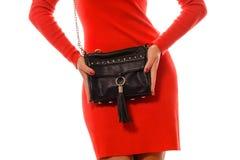 Moderne Frau mit schwarzer Tasche in den Händen und im roten Kleid Stockfotografie