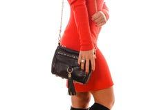 Moderne Frau mit schwarzer Tasche in den Händen und im roten Kleid Lizenzfreie Stockfotos
