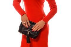Moderne Frau mit schwarzer Tasche in den Händen und im roten Kleid Stockbild