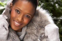 Moderne Frauen-tragender Pelz-Mantel im Studio stockfoto