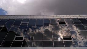 Moderne Gebäudedetails in den kalten Farben mit Reflexion von weißen Wolken Stockfoto