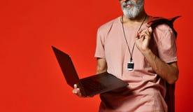 Moderne gelukkige modieuze bejaarde hogere mannelijke smeltende laptop computer royalty-vrije stock foto's