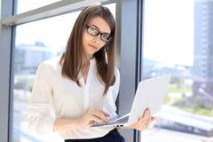 Moderne Geschäftsfrau, die auf Laptop-Computer bei der Stellung im Büro vor dem Treffen oder Darstellung schreibt Stockfoto