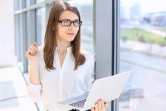 Moderne Geschäftsfrau, die auf Laptop-Computer bei der Stellung im Büro vor dem Treffen oder Darstellung schreibt Stockfotos