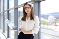 Moderne Geschäftsfrau, die auf Laptop-Computer bei der Stellung im Büro vor dem Treffen oder Darstellung schreibt Lizenzfreie Stockbilder