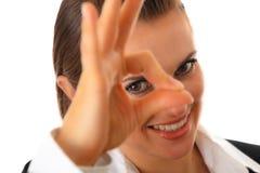 Moderne Geschäftsfrau, die durch okaygeste schaut Stockfoto