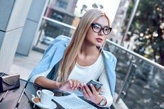 Moderne Geschäftsfrau, die in einem Café gedacht an weitere Aussichten sitzt lizenzfreie stockfotos