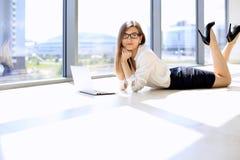 Moderne Geschäftsfrau, die mit Laptop-Computer beim Lügen am Boden im Büro, Kopienraum arbeitet Lizenzfreie Stockfotos