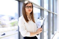Moderne Geschäftsfrau, die Papiere im Büro mit Kopienraumbereich steht und hält Lizenzfreie Stockbilder
