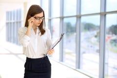 Moderne Geschäftsfrau, die Papiere im Büro mit Kopienraumbereich steht und hält Stockfotos