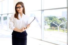 Moderne Geschäftsfrau, die Papiere im Büro mit Kopienraumbereich steht und hält Stockbilder