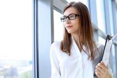 Moderne Geschäftsfrau, die Papiere im Büro mit Kopienraumbereich steht und hält Stockbild