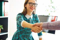 Moderne Geschäftsfrau mit dem Arm verlängerte auf Händedruck Stockfotografie