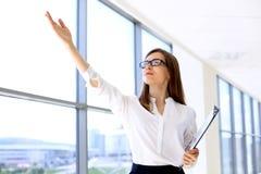 Moderne Geschäftsfrau zeigt oben durch ihre Hand bei der Stellung im Büro Stockbilder