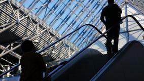 Moderne glas de bouw en het bewegen zich silhouetten van bedrijfspersonen op roltrap stock videobeelden