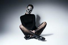 Moderne gotische Frau, die auf dem Boden sitzt Stockfoto