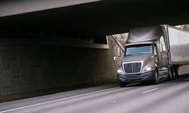 Moderne grijze semi vrachtwagen onder brug op weg tusen staten Stock Foto