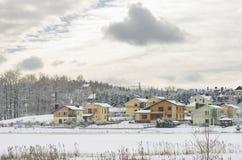 Moderne Häuser durch den gefrorenen See im Winter Lizenzfreies Stockbild