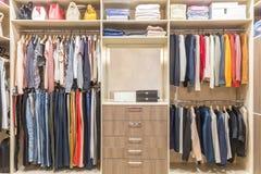 Moderne hölzerne Garderobe mit der Kleidung, die an der Schiene im Weg im Wandschrank hängt stockfotos