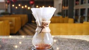 Moderne hand gebrouwen koffie Barista brouwt koffie gebruikend koffiezetapparaat Sluit omhoog dalingen van koffie die van documen stock videobeelden