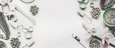 Moderne Hautpflegekosmetik, die mit Schönheitsausrüstungs- und -orchideenblumen verfassen Ebene legen auf weißen Schreibtischhint lizenzfreie stockfotos