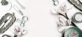 Moderne Hautpflegekosmetik, die mit Schönheitsausrüstungs- und -orchideenblumen verfassen Ebene legen auf weißen Hintergrund, Dra lizenzfreie stockbilder