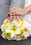 Moderne Hochzeitshände und -ringe auf Blumen Stockfotografie