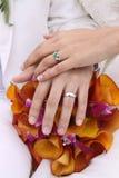 Moderne Hochzeitshände und -ringe auf BlumeStrand Stockfotos