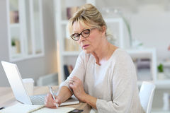 Moderne hogere vrouw die aan laptop werken stock fotografie