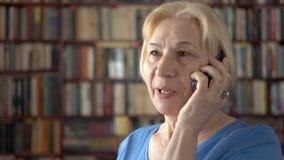 Moderne hogere vrouw die thuis cellphone gebruiken, die met vriend spreken Boekenkastboekenrekken op achtergrond stock videobeelden
