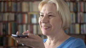 Moderne hogere vrouw die thuis cellphone gebruiken, die met vriend spreken Boekenkastboekenrekken op achtergrond stock video